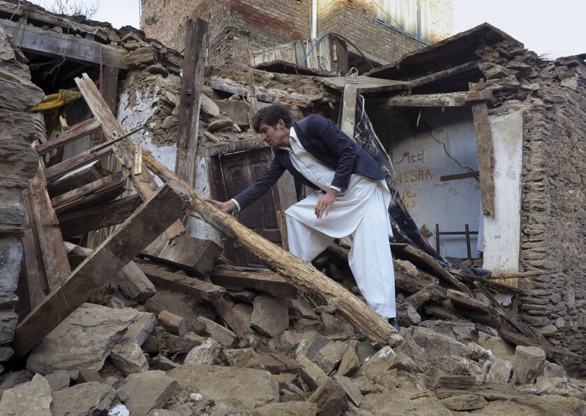 A Pakistani boy climbs through the rubble of a damaged house in Mingora in the Swat Valley. Officials say rescuers are struggling to reach quake-stricken regions in Pakistan and Afghanistan.