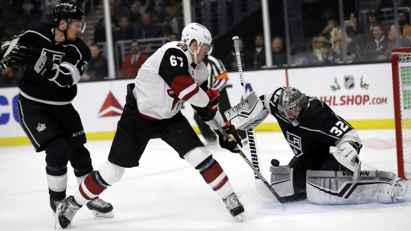 Arizona Coyotes' Lawson Crouse, center, scores past Kings goaltender Jonathan Quick (32) during the first period.