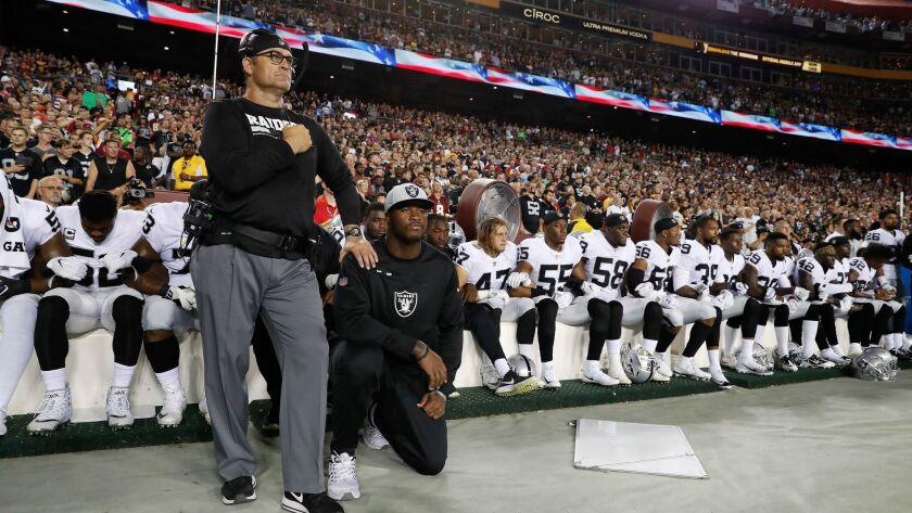 Some members of the Oakland Raiders kneel during the playing of the National Anthem before an NFL fo
