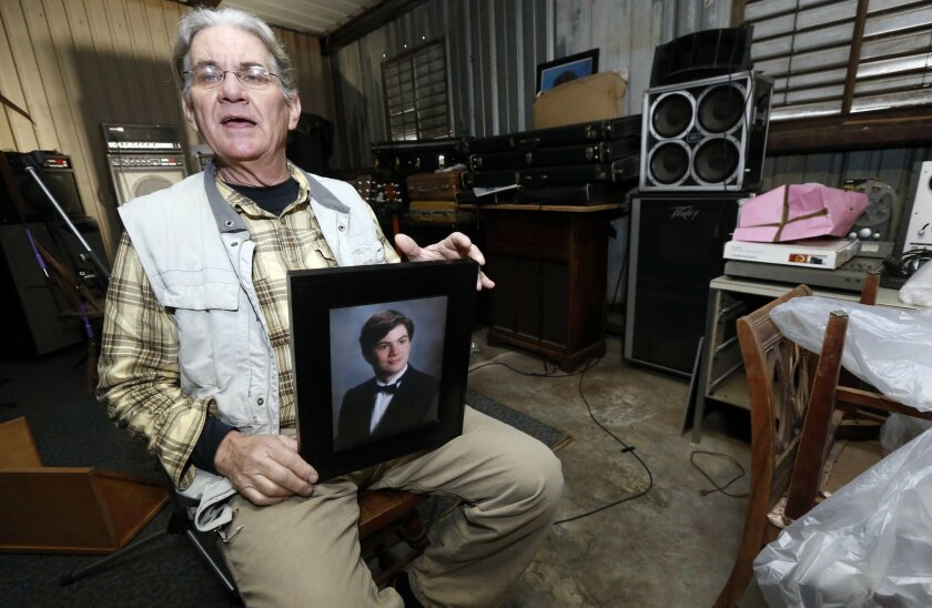 In this March 20, 2016 photograph, Michael Usry Sr. holds a portrait of his then 19-year-old son, Michael Jr., at his Clinton, Miss., garage. Usry recalls how his son became a prime suspect for a short time in a Idaho Falls murder and rape case, although never charged, because of DNA Usry donated to a genealogical research effort backed by the Mormon Church and operated by Brigham Young University scientists as part of the church's deep involvement in genetic research. (AP Photo/Rogelio V. Solis)