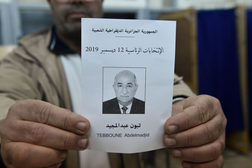 An election official displays a paper ballot featuring a photo of Abdelmadjid Tebboune during the counting process in Algiers on Thursday.