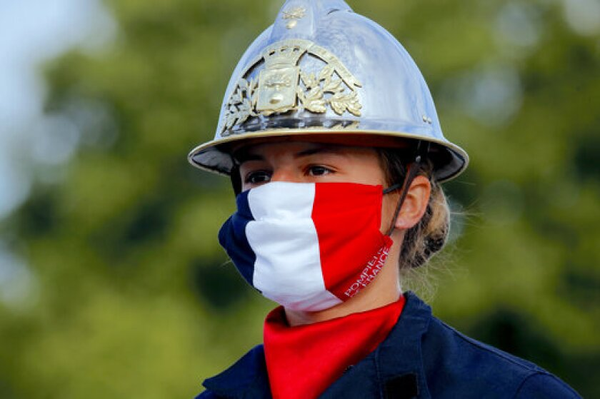 FILE - In this July 14, 2020, file photo, a firefighter wears a face mask with the colors of the French flag, prior to the Bastille Day parade on the Champs-Élysées avenue in Paris. Masks made of cotton and other washable materials have become a big seller as face coverings have emerged as one of the most effective ways to prevent further spread of the coronavirus. (AP Photo/Christophe Ena, Pool)