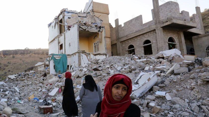 Yemeni women walk through the debris of a housing block allegedly destroyed by previous Saudi-led airstrikes in Sana'a, Yemen on Sept. 29.