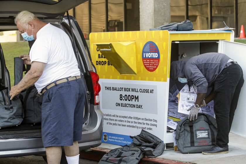 A worker bends over to move ballots from a drop box into gray bags as another worker loads bags into the back of a van