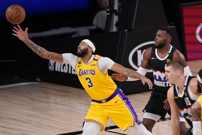 Anthony Davis, de los Lakers de Los Ángeles, se estira en busca de un balón durante el encuentro de playoffs disputado el jueves 24 de septiembre de 2020, ante los Nuggets de Denver, en Lake Buena Vista, Florida (AP Foto/Mark J. Terrill)