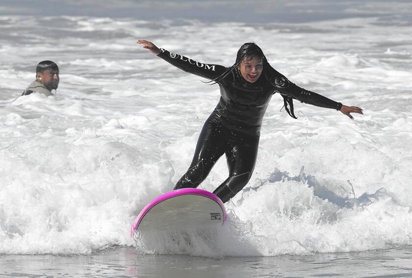 Jackie Olivares gets to her feet during Save Our Youth's Surf Days program in west Newport on Thursday.
