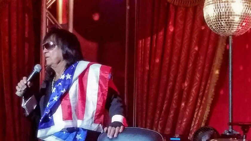 Lounge singer Cook E. Jarr onstage with microphone in hand and an American flag draped over his shoulder.