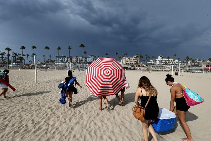 Beachgoers evacuate Huntington Beach because of potential lightning with a monsoon thunderstorm in August 2017.