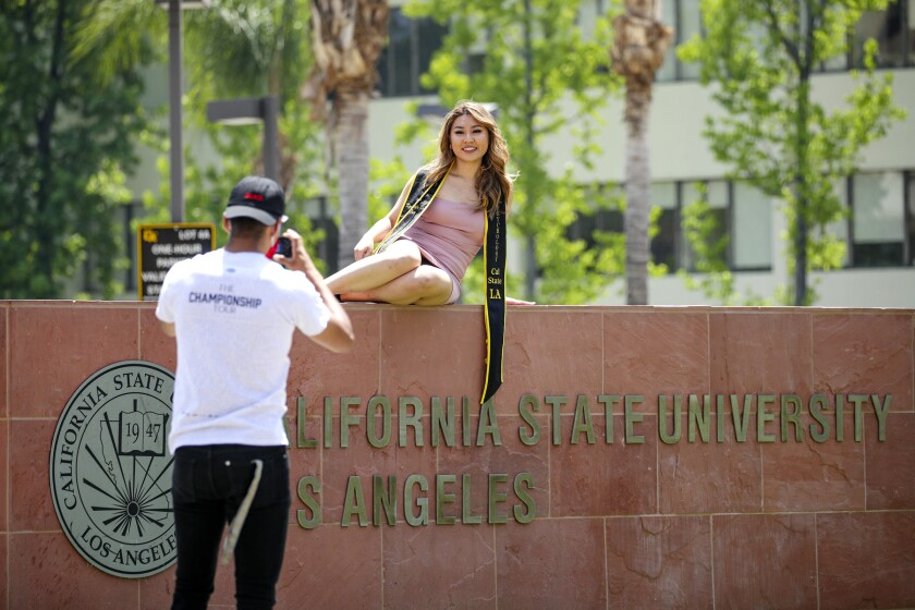 Cal State LA student wearing a graduation sash poses for photo