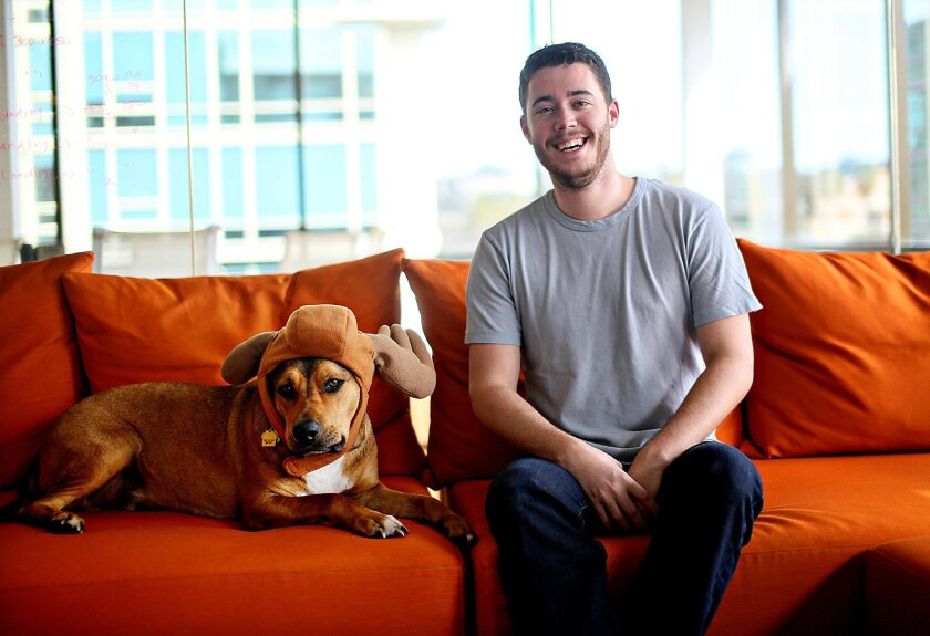 Stephan Goss, CEO of Zeeto Media, seated with one of his canine buddies, encourages employees to bring their pets to work.