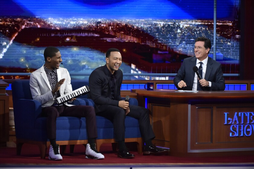 """Stephen Colbert, right, with bandleader Jon Batiste, left, and guest John Legend on CBS' """"The Late Show."""""""