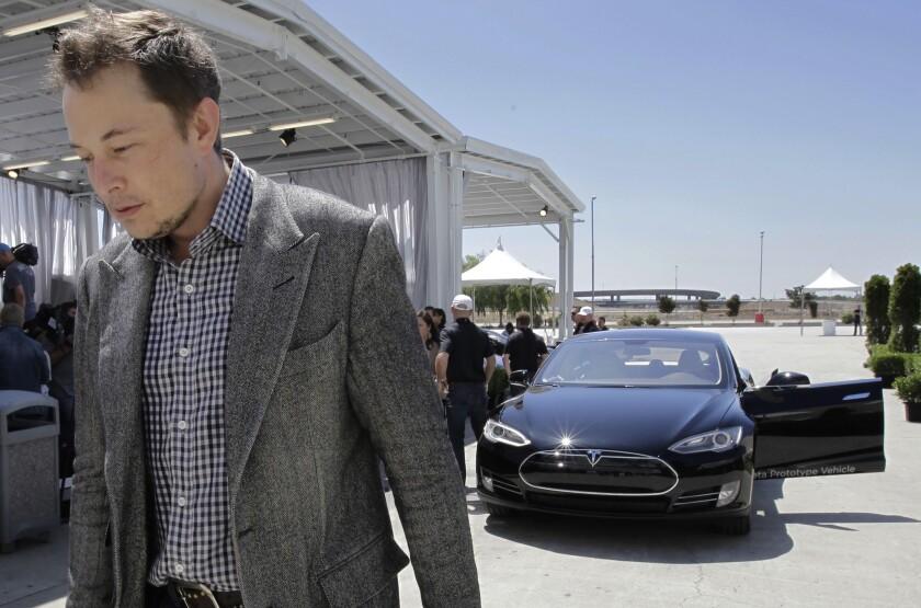 Tesla CEO Elon Musk walks past a Tesla Model S at the automaker's factory in Fremont, Calif.