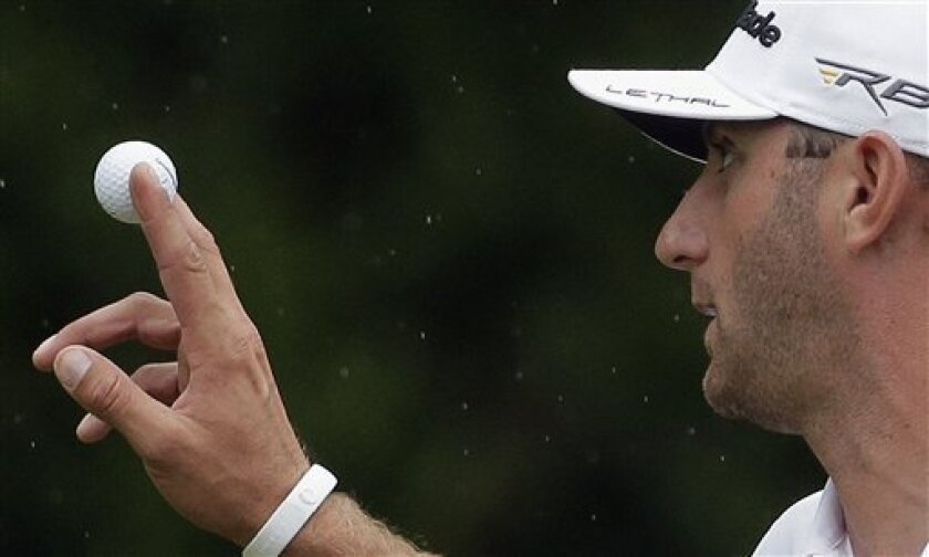 Dustin Johnson holds up his ball after a birdie on the fourth hole during the second round of the Masters golf tournament Friday, April 12, 2013, in Augusta, Ga. (AP Photo/Charlie Riedel)