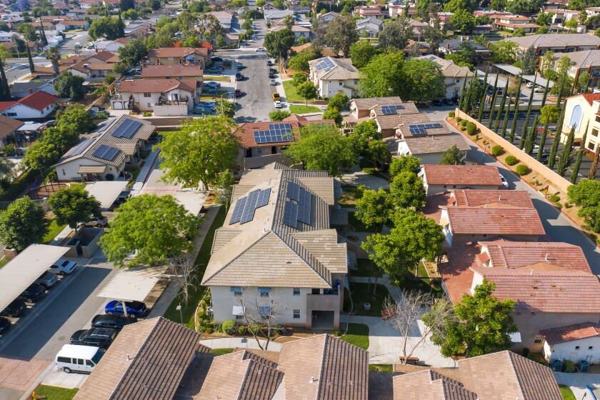 An aerial view of houses with solar panels on their roofs.