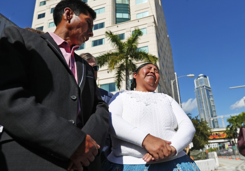 Eloy Rojas Mamani, left, looks on as his wife Etelvina Ramos Mamani speaks during a news conference after leaving the 11th U.S. Circuit Court of Appeals, Tuesday, Nov. 19, 2019, in Miami. A group of indigenous Bolivians want the appeals court to restore a $10 million jury verdict against the former president and defense minister of the South American nation over killings by security forces during 2003 unrest there. The Mamani's are the parents of eight-year-old Marlene, who was shot by a soldier in 2003. (AP Photo/Wilfredo Lee)