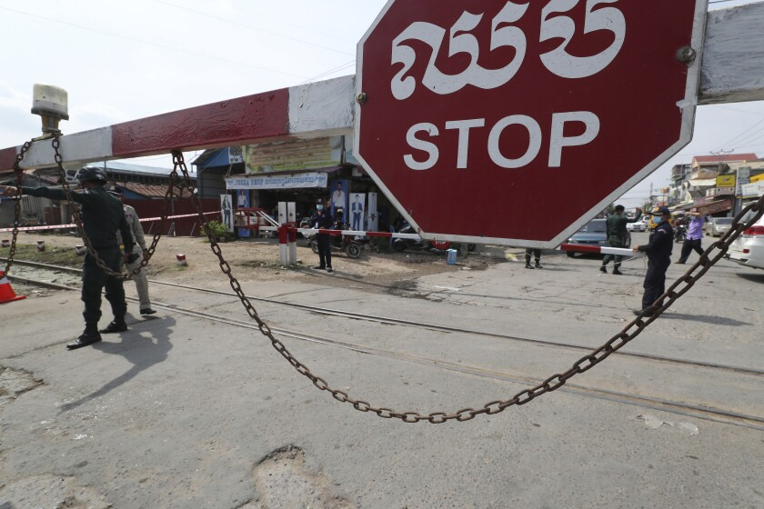 Local police officers stand guard at a blocked street near Phnom Penh International airport in Phnom Penh, Cambodia, Thursday, April 15, 2021. Cambodia's leader said that the country's capital Phnom Penh will be locked down for two weeks from Thursday following a sharp rise in COVID-19 cases. (AP Photo/Heng Sinith)