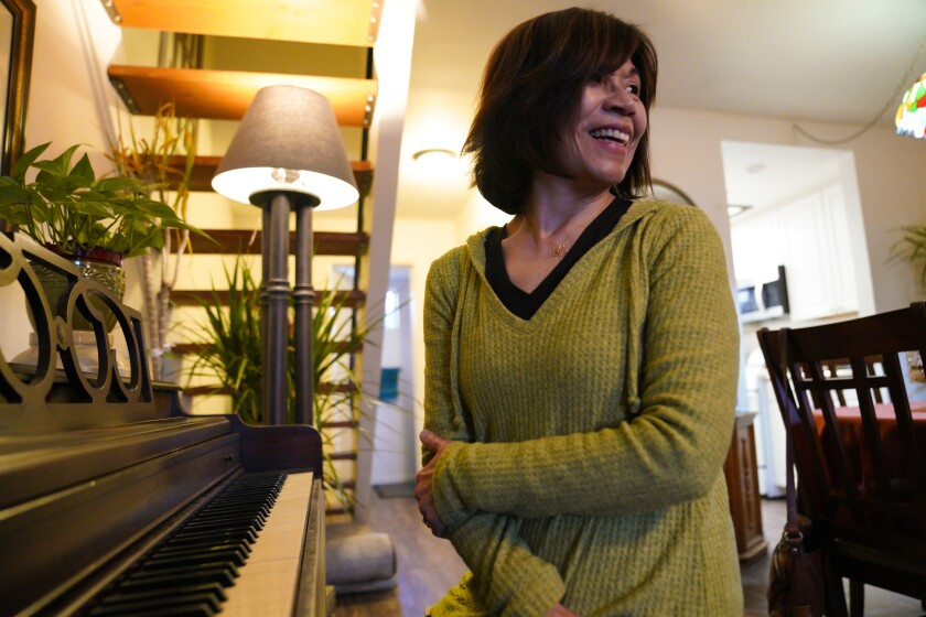 At her home in Santee, Carmen Kcomt relaxes playing the piano after a day at the office.