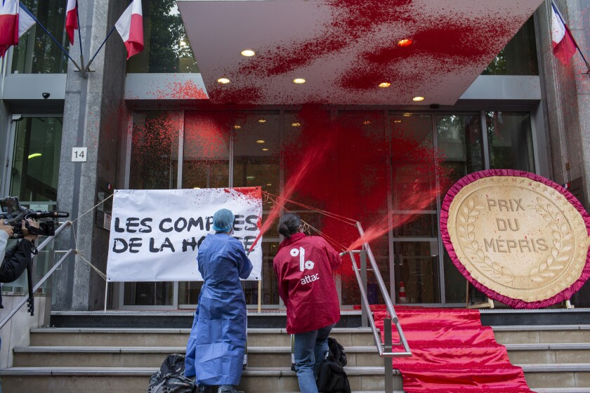 French activists of Attac stage a flash protest outside the French Health Ministry in support of medical workers, in Paris, France, Saturday, June 20, 2020. French hospital workers and others are protesting to demand better pay and more investment in France's public hospital system, which is considered among the world's best but struggled to handle a flux of virus patients after years of cost cuts. (AP Photo/Rafael Yaghobzadeh)