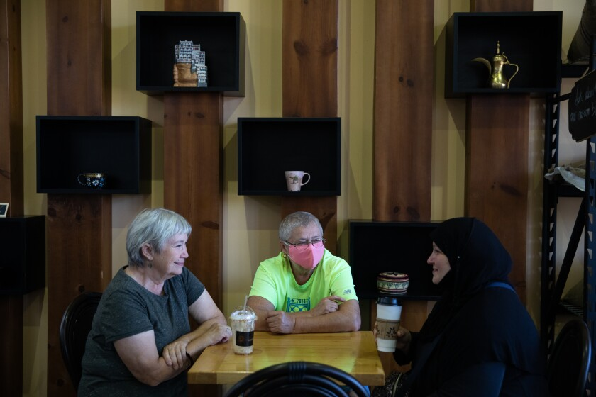 Three people chat over coffee