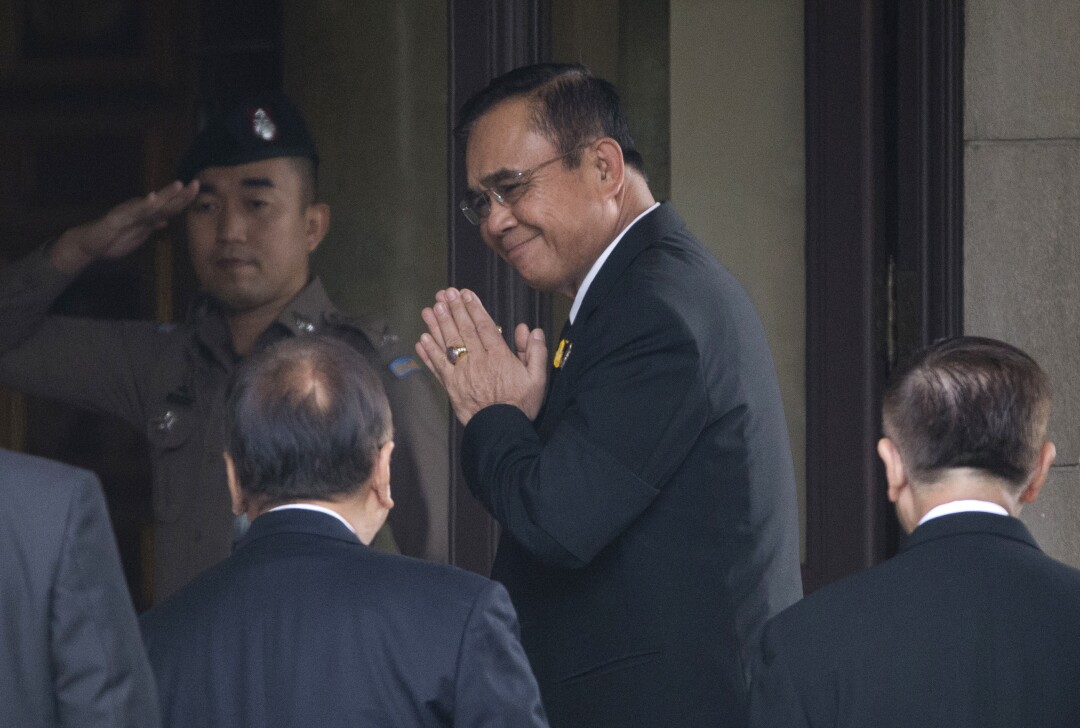 Thailand's Prime Minister Prayuth Chan-ocha arrives at a building guarded by a man in uniform
