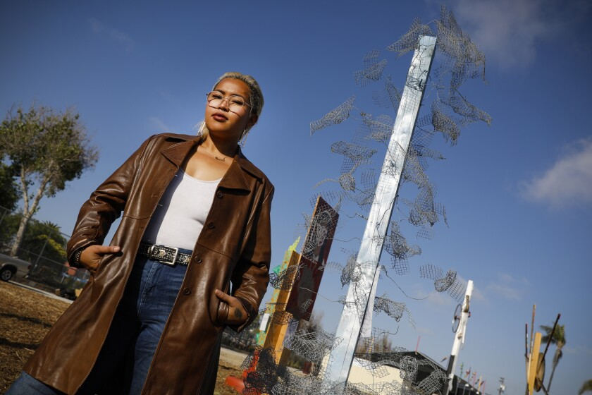"Tarrah Aroonsakool stands near her tall, metallic-looking sculpture that juts into the sky. It's called ""Resilience."""