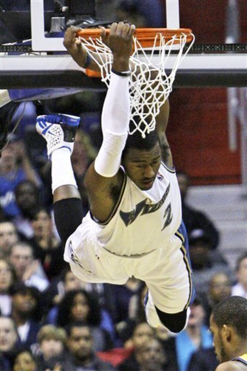 Washington Wizards guard John Wall (2) swings from the rim after dunking against the New Orleans Hornets in the first quarter of an NBA basketball game in Washington, on Saturday, Jan. 1, 2011. (AP Photo/Jacquelyn Martin)