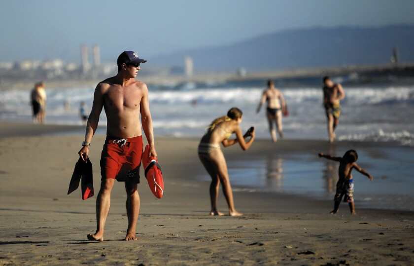 L.A. County lifeguard Morgan Wallace watches the water next to the pier in Venice. During the peak of a heat wave in September, lifeguards made 187 rescues in a single day -- 88 of them at Venice Beach alone.