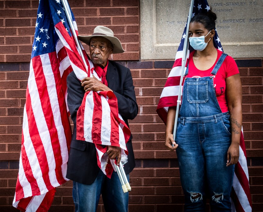 Two people hold flags near the entrance of a church in Atlanta.