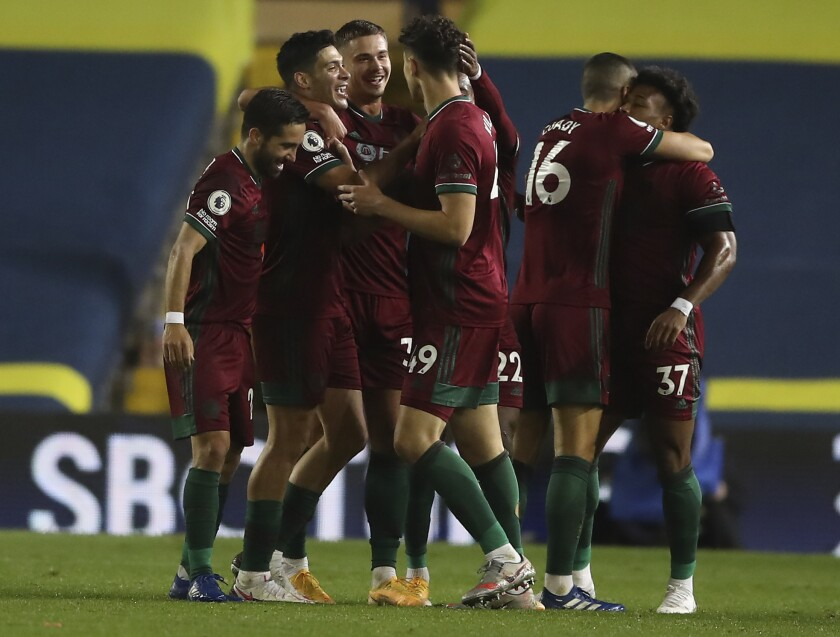 Wolverhampton Wanderers' Raul Jimenez, 2nd left, celebrates with his teammates after scoring during the English Premier League soccer match between Leeds United and Wolverhampton Wanderers at Elland Road ground in Leeds, England, Monday, Oct. 19, 2020. (Martin Rickett/Pool via AP)