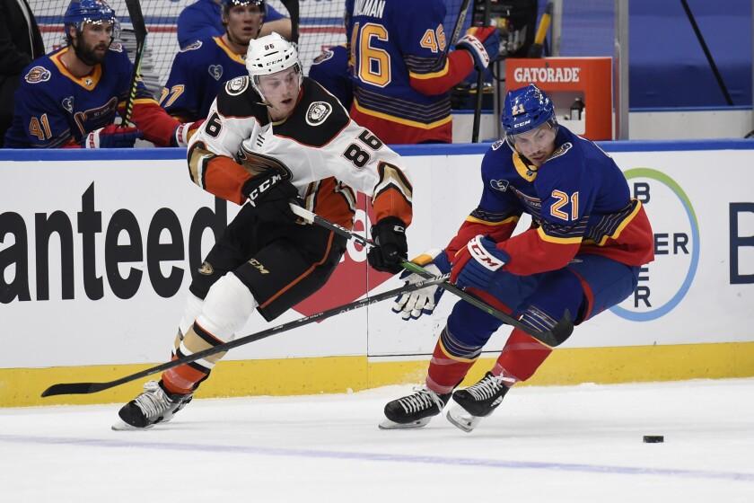 Ducks' Simon Benoit and St. Louis Blues' Tyler Bozak battle for the puck.