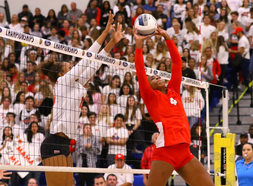Redondo's Kami Miner (4) looks to set the volleyball while Mater Dei's Zaria Henderson (13) is ready for a block at the net.