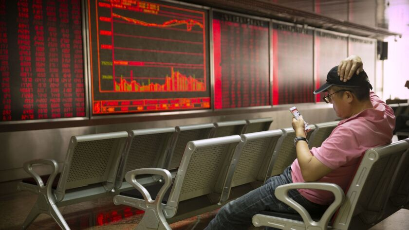 A Chinese investor uses his smartphone as he monitors stock prices at a brokerage house in Beijing,