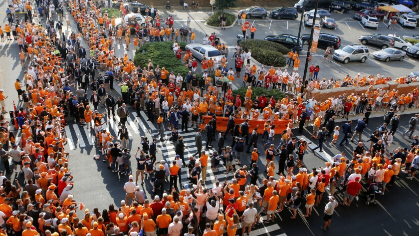 FILE - In this Oct. 5, 2019, file photo, Tennessee players and coaches take part in the Vol Walk at Neyland Stadium before the team's NCAA college football game against Georgia in Knoxville, Tenn. Pre-game traditions are making a return this season, like Tennessee's pre-game Vol Walk, minus the high-fives or any other physical contact with players. No masks will be required--just encouraged--inside Neyland Stadium, the nation's fifth-largest stadium. (C.B. Schmelter/Chattanooga Times Free Press via AP, File)