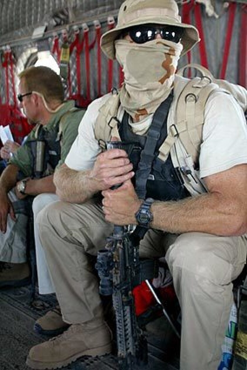 U.S. private security officers are shown in 2003 in a Chinook helicopter that was guarding L. Paul Bremer, Iraq's U.S. civilian administrator at the time, as he ventured near the city of Basra. Tens of thousands of such employees operate in the war-torn country. Today, the Interior Ministry canceled the license of the American security firm Blackwater USA after officials charged that eight civilians were shot and killed Sunday by company bodyguards accompanying a U.S. State Department motorcade. American officials are launching an investigation in conjunction with Iraq, a spokeswoman said.