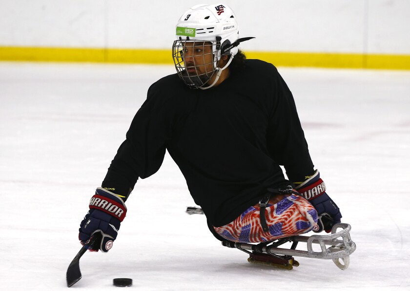 Ralph DeQuebec, a Paralympic hockey gold medalist from Harbor City, participates in a sled hockey clinicat Great Park Ice rinks in Irvine on Saturday.