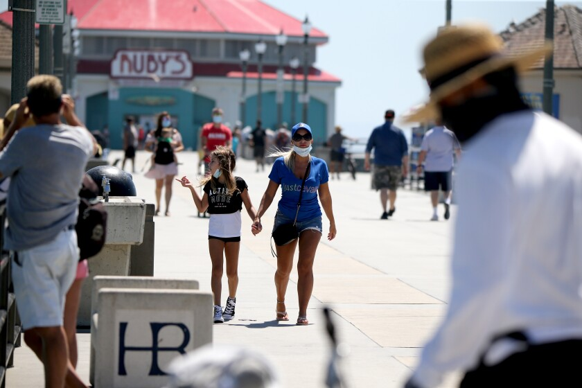 Visitors to the pier wear face masks, in Huntington Beach on Friday, July 31, 2020.