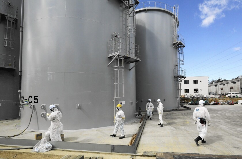 Workers check storage tanks of radiation-contaminated water at Tokyo Electric Power Co.'s tsunami-crippled Fukushima Daiichi nuclear plant.
