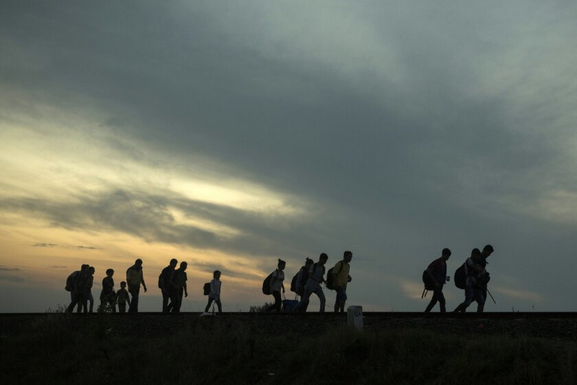 FILE - This is a Thursday Sept. 3, 2015 file photo of a group of refugees as they walk along the railway tracks near the town of Roszke, Hungary, after crossing the border from Serbia. Among the tens of thousands fleeing war and despair in the Middle East, one group feels a special relief in reaching Europe: those who have escaped areas ruled by Islamic State extremists and the harsh scrutiny of their religious police. (AP Photo/Santi Palacios, File)