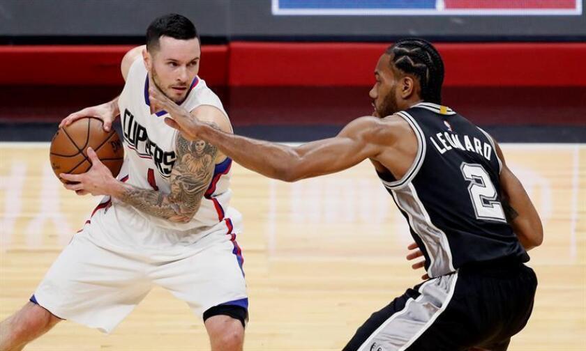 El jugador de los Clippers de Los Ángeles J.J Redick (i) defiende la bola frente a Kawhi Leonard, de los Spurs de San Antonio. EFE/Archivo
