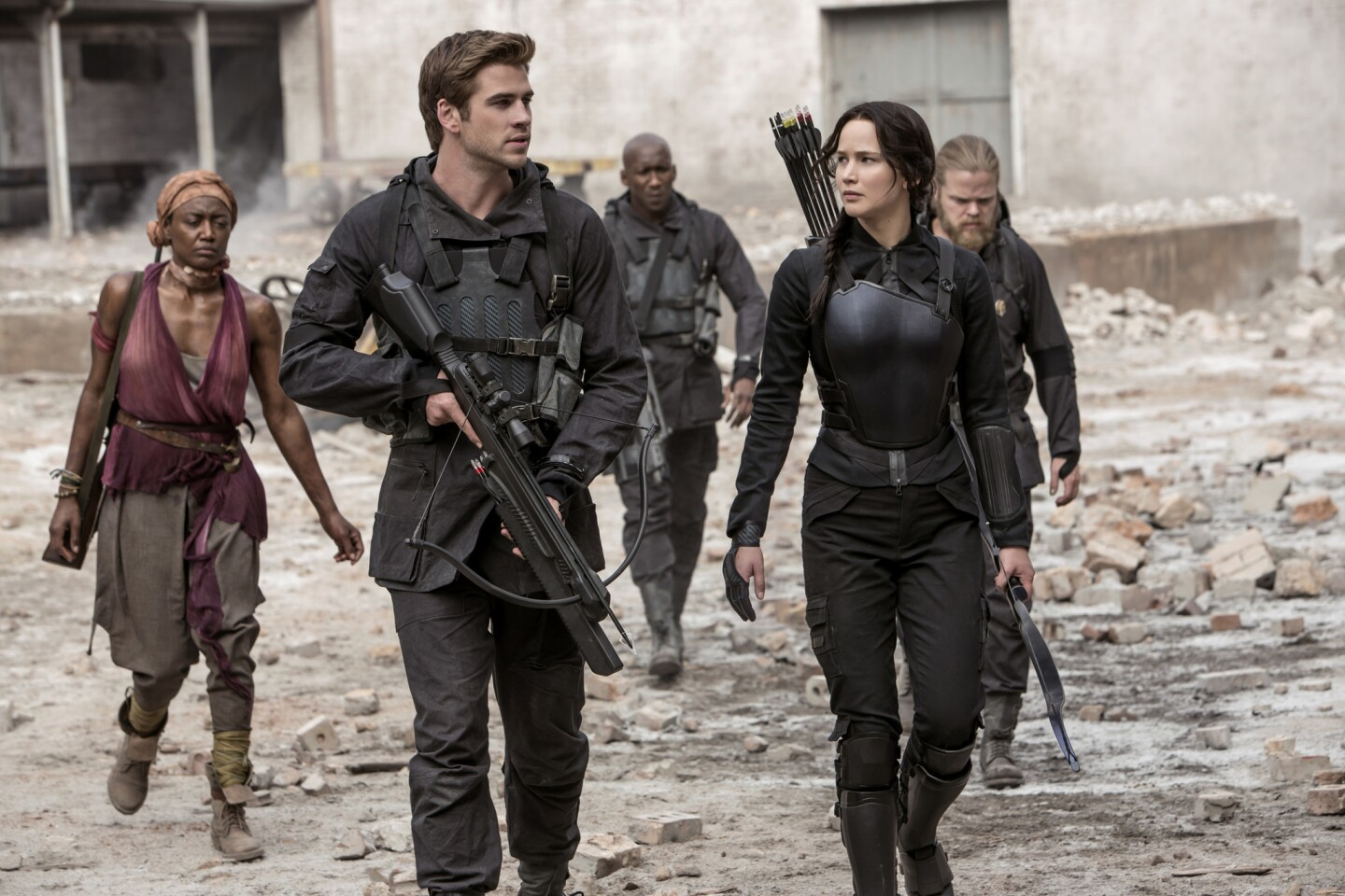 Liam Hemsworth as Gale Hawthorne, Jennifer Lawrence as Katniss Everdeen, and other cast members in costumes by Kurt & Bart in The Hunger Games Mockingjay Part 1.