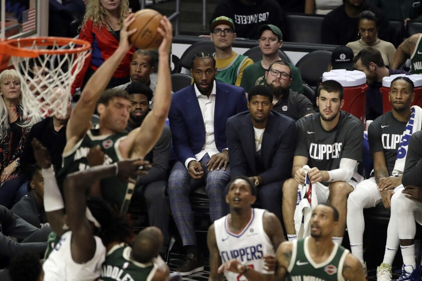 Los Angeles Clippers' Kawhi Leonard, center, and Paul George, third from right, watch from the bench during the second half of the team's NBA basketball game against the Milwaukee Bucks on Wednesday, Nov. 6, 2019, in Los Angeles. (AP Photo/Marcio Jose Sanchez)