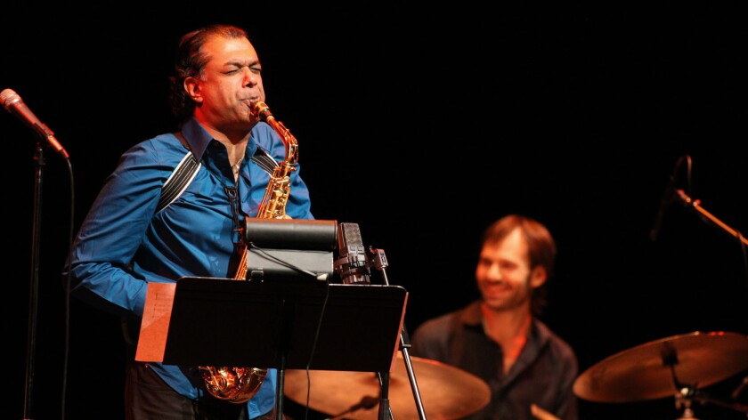 Saxophonist Rudresh Mahanthappa and drummer Dan Weiss are shown performing at a Los Angeles concert.