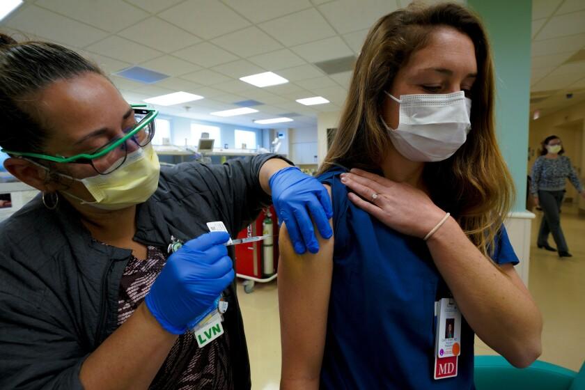 Una enfermera  vacuna a una doctora.