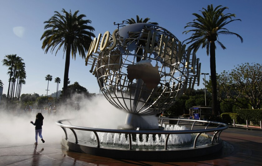 A girl runs through the spray at the entrance of Universal Studios Hollywood. The park in Los Angeles and the Universal Orlando Resort will stay closed until at least May 31.