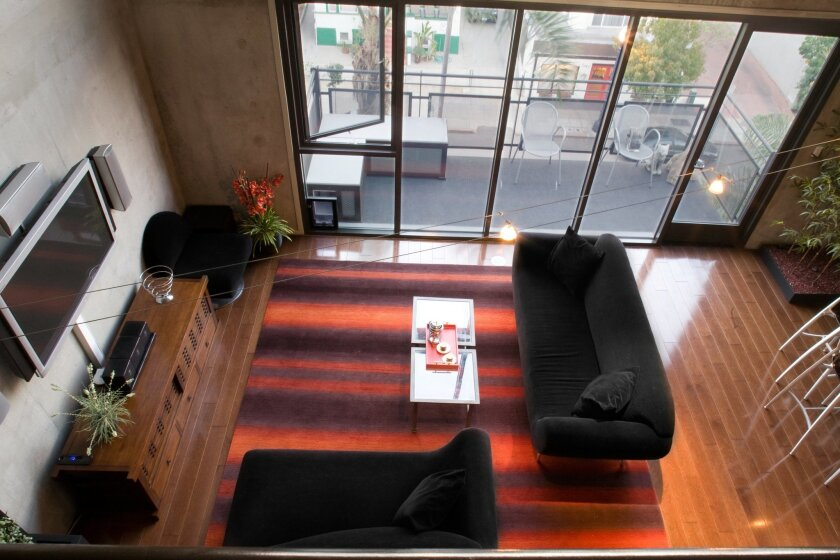 The living room of a two-story loft in Little Italy reflects the resident's desire for clean, Asian-style design.