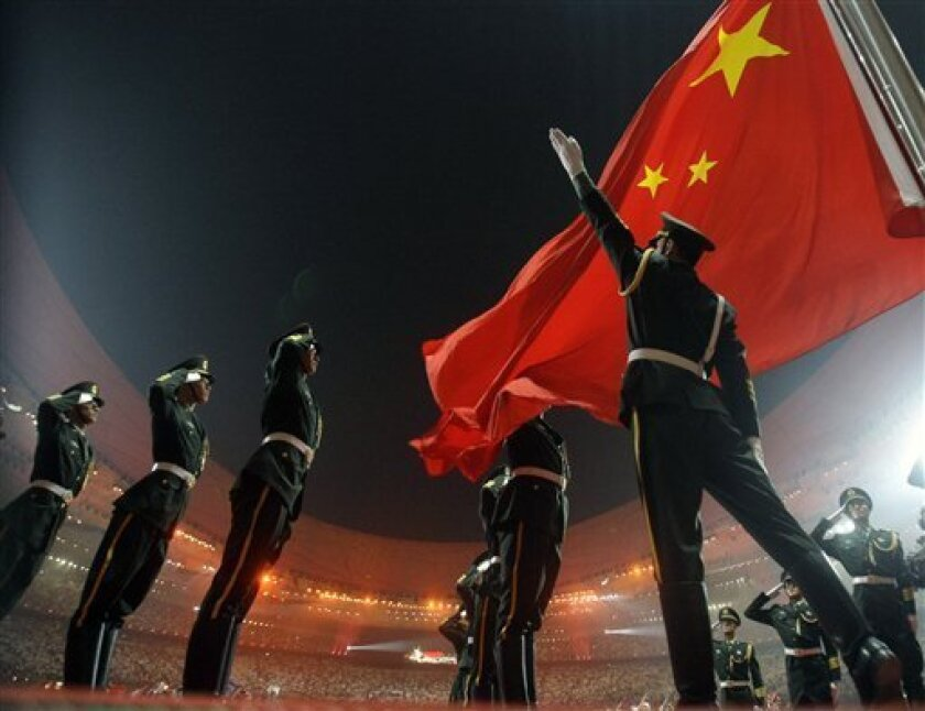 In this Aug. 8, 2008 file photo, Chinese military soldiers salute as the Chinese flag is raised during the Opening Ceremony for the Beijing 2008 Olympic Games in Beijing, China. China said Tuesday, Jan. 20, 2009, that its overall security situation had improved over the past year, although it rem