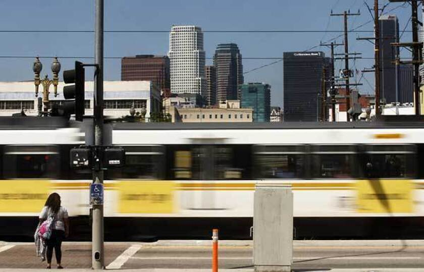 A Metro Blue Line train zips past a pedestrian near Washington Boulevard and Flower Street. Metro is offering free fares Tuesday on all buses and trains.