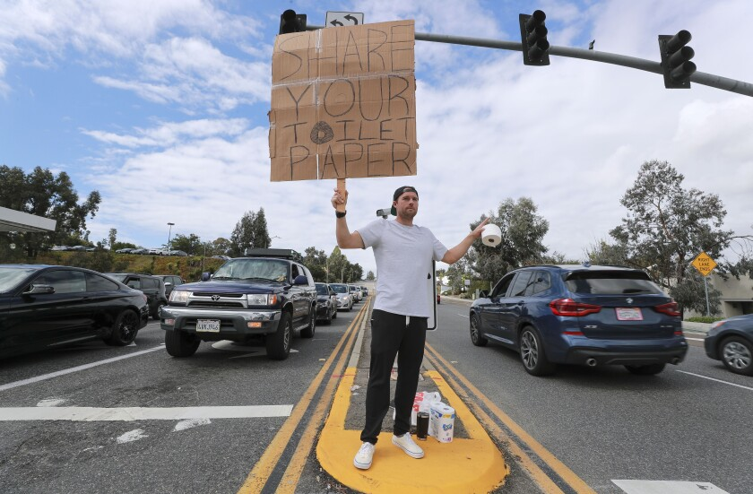 Encinitas resident Jonny Blue, 33, who is a physical therapist, makes a request for toilet paper so that he can in turn give it to drivers that need it while standing at the intersection of Encinitas Boulevard and El Camino Real on Saturday, March 14, 2020 in Encinitas, California.