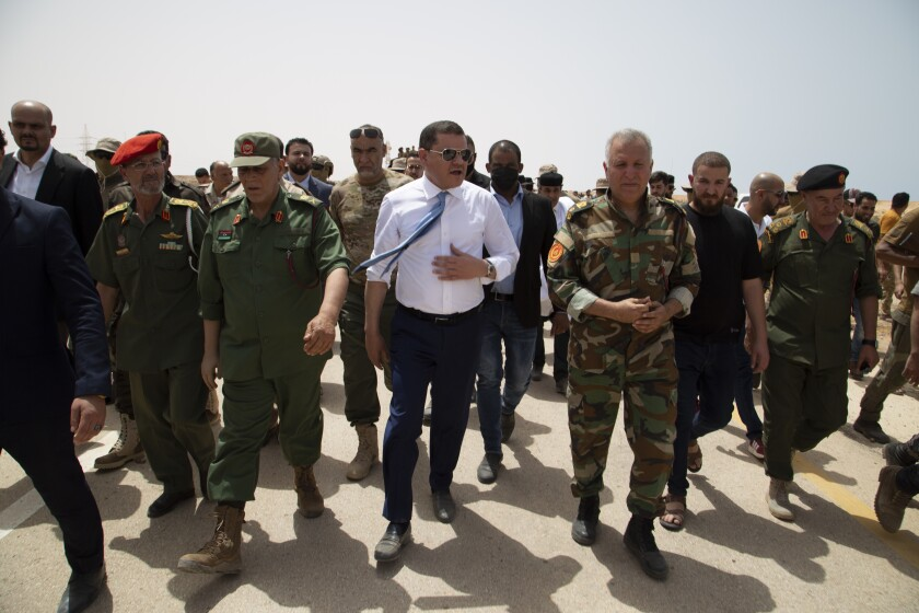 Libyan Prime Minister Prime Minister Abdul Hamid Dbeibah attends the reopening of the road between the cities of Misrata and Sirte Sunday, June 20, 2021. Libya's interim authorities reopened on Sunday the Mediterranean coastal highway linking the country's long-divided eastern and western cities, in the latest bid to reunite the territories after years of civil war. (AP Photo/Yousef Murad)