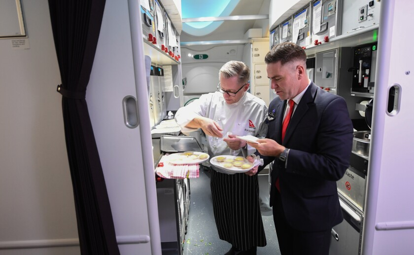 Two crew members, one in a chef's jacket and the other in a suit, in the galley with plates of food.